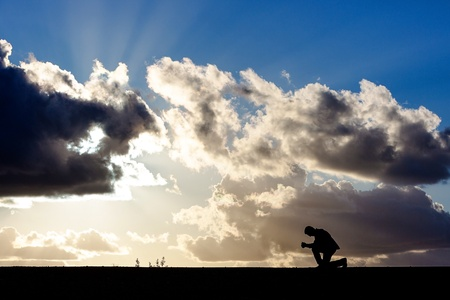 man kneeling in prayer before a dramatic sky Stock Photo