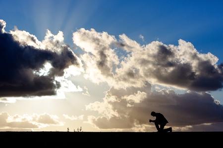 humility: uomo inginocchiato in preghiera davanti a un cielo drammatico