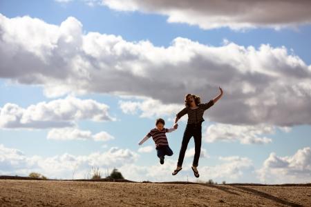 gelukkige kinderen springen van vreugde met mooie bewolkte achtergrond