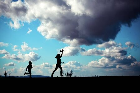 silhouette of children running with toy airplane photo
