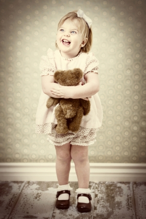 vintage little girl hugging her teddy bear photo