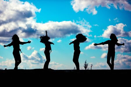 silhouette of a young girl dancing against a dramatic sky photo