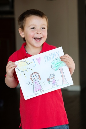 adoration: Happy child holds out his art work for Mommy Stock Photo