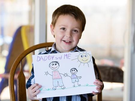 Niño feliz tiende la obra de arte para papá Foto de archivo - 18626380