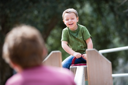 totter: Happy little boy playing on a teeter totter