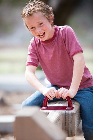 totter: Happy boy laughing as he plays on a playground teeter totter
