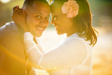 sincere girl: Beautiful couple embracing  in a rainbow of sunlight Stock Photo