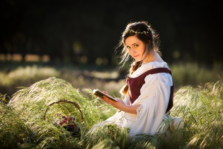 Beautiful girl in historical costume reading a book