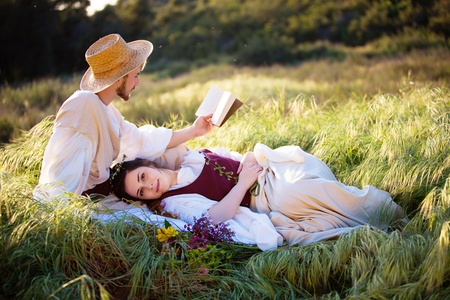 historical clothing: Historical couple reading in an open field