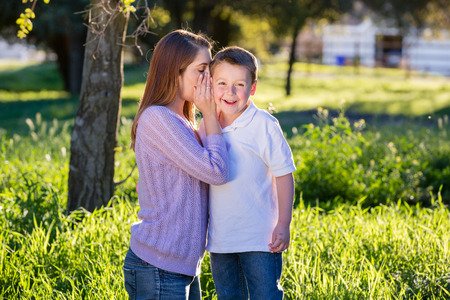 thankful: Mother whispering into her little boy\
