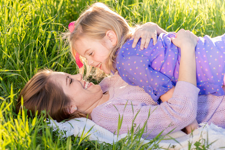 Mother and daughter snuggling in the sunshine Stock Photo
