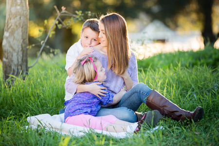 Happy mother snuggling her children