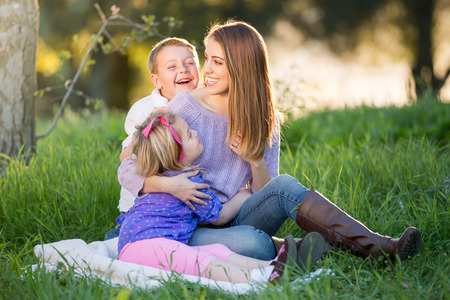 family tickle: Happy mother playing with children Stock Photo