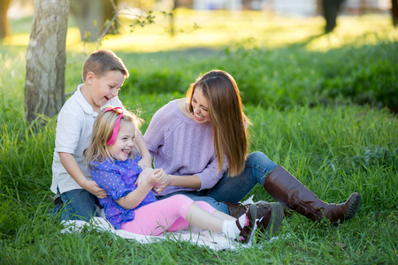 Happy mother and children playing in the grass