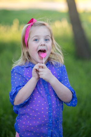 Happy little girl with a heart shaped lollipop Stock Photo