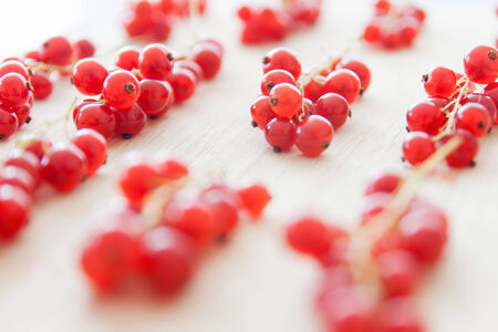 Redcurrant bunches on light wood plate  Close-up photo