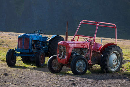 Two old tractors, blue tractor and red tractor in Iceland