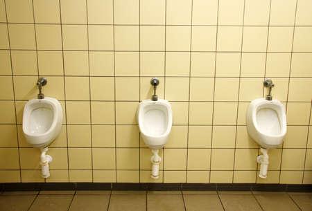 Three white ceramic urinals on yellow wall