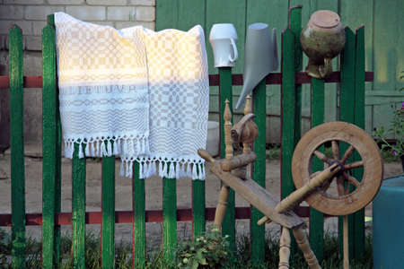 Traditional spinning wheel in Lithuania near green wooden fence with spined fabric.