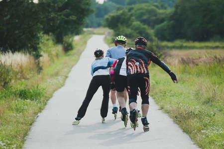 Four older people riding on roller skates in line at summer time