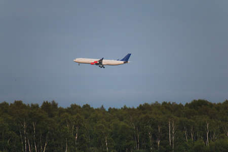 AIrplane flies over the forest Kastrup summer season Reklamní fotografie - 122352365