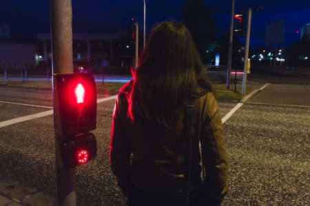 Girl waiting to cross a street in night red light is shining - Reykjavik Iceland Reklamní fotografie - 122352381