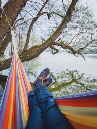 Man with blue shoes and jeans swings in colorful hammock hangs on shore of the lake at spring time in Denmark