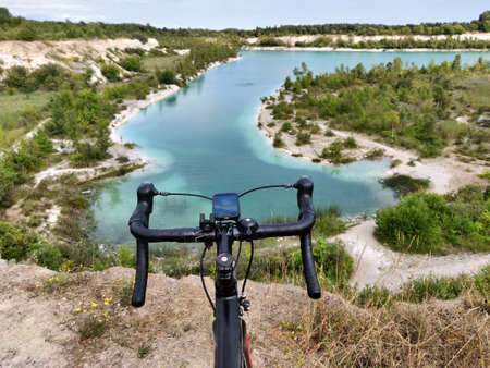 Black road bicycle on the edge of cliff blue lake in front Denmark, Kalk grav at summer time