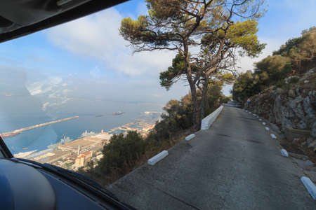 Road on the edge of cliff drive to The Rock Gibraltar harbor summer season