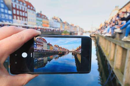Caucasian man capturing photo of Nyhavn in Copenhagen during Sankthans fest celebration Reklamní fotografie