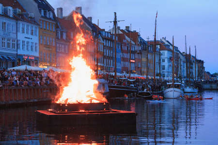Copenhagen, Zealand / Denmark - June 23 2019: Burning The witch on bonfire the middle of Nyhavn canal during Sankthans evning Editorial