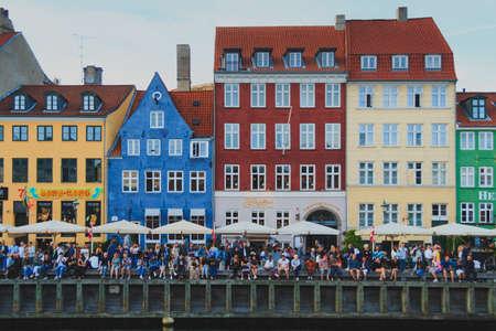 Copenhagen, Zealand / Denmark - June 23 2019: Many people sit along the edge of the Nyhavn canal waiting Saint Johns Eve bonfire