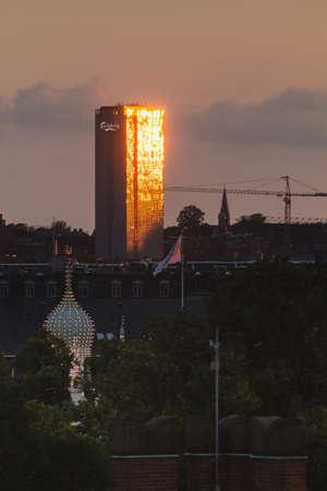 Copenhagen, Zealand  Denmark - June 27 2019: The Headquarters of Carlsberg company in the capital city of Denmark, Copenhagen sunset reflects on building glass windows