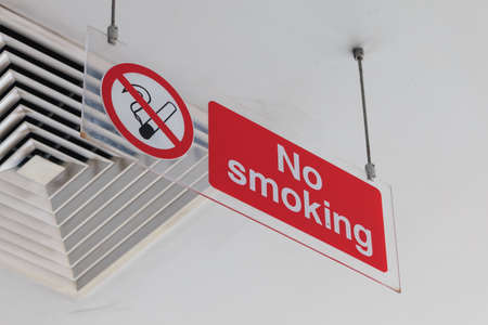 Acrylic no smoking sign attached on ceiling. View from below