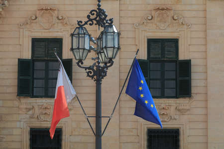Malta national flag Europe union flag hang in front of old historic building in Valletta Malta Banco de Imagens - 130591953