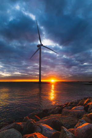 Windmill in Denmark at contrastive sunset blue dark sky Stock Photo