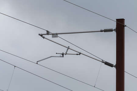 Overhead live electric supply metal pole with electric wires. Close-up angle