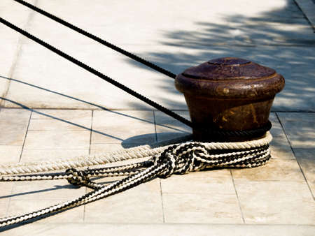 steadiness: Harbor bollard (dock part) with ropes on it. Concept for strength and steadiness. Stock Photo