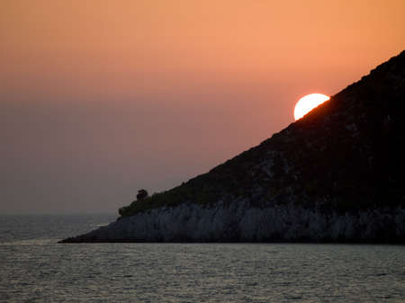 wind down: Interesting sunset with sun going down behind triangle shape coast. Stock Photo