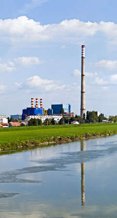 Heating and power plant near river against blue sky and green plants photo
