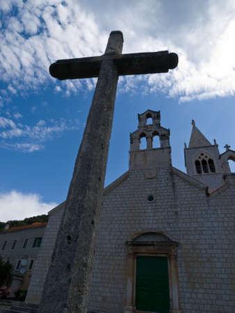 Big stone cross in front of the old church in village Lastovo, Croatia Stock Photo - 3250997