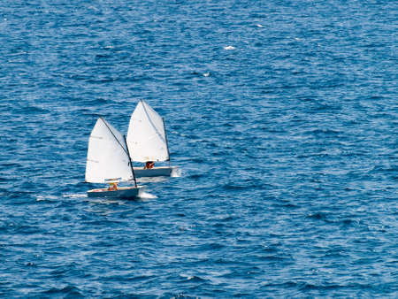 yacht race: Small racing sailboat in class optimist. Training and practice. Stock Photo