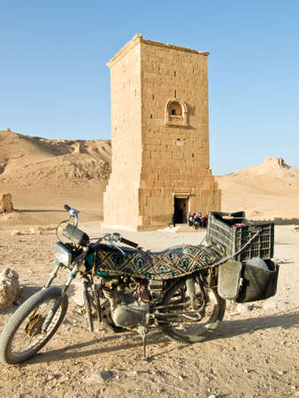 remains: Old local motorbike in front of tombs in  Palmyra (Tadmor), Syria. Ancient Period tombs. Stock Photo