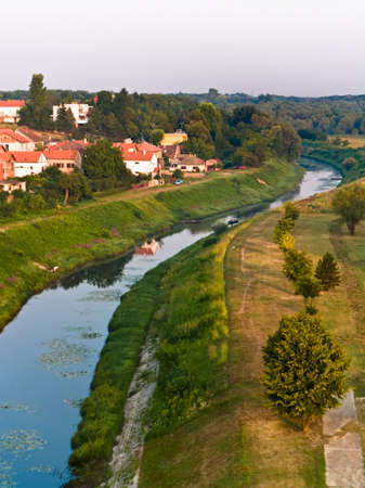 reflecting: Small river in the town Vukovar, Croatia. Early morning.