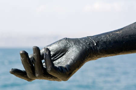 Hand covered with mud from Dead sea, Jordan. Skincare treatment. Use of high depth of field to blur the background. photo