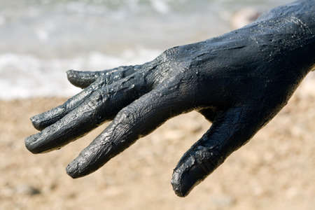 Hand covered with mud from Dead sea, Jordan. Skincare treatment. Use of high depth of field to blur the background. Stock Photo - 4229134