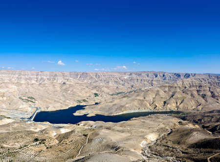 artificially: Wadi Mujib - King s road area, highway  on the water dam with desert landscape around it in Jordan. Stock Photo