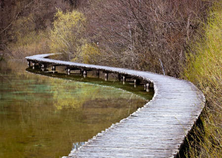 long lake: Curved wooden path in the Plitvice lakes (Plitvicka jezera) national park, Croatia, Europe. Season: Early spring. Stock Photo