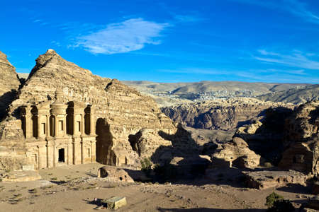 khazneh: Petra - Nabataeans capital city (Al Khazneh) , Jordan. Monastery tomb with bedouin new village in background at distance. Roman Empire period. Panorama from top of the hill. Stock Photo