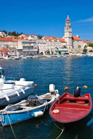 brac: Sutivan on Island Brac in Croatia. Made of well known white limestone. Small port with fishing boats in front Stock Photo